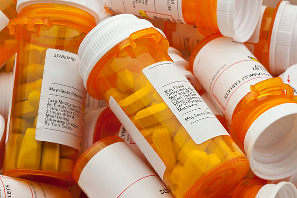 Several Prescription Pill Bottles in a Pile Bottles of prescription medicine in a pile. This collection of pill bottles is symbolic of the many medications senior adults and chronically ill people take. generic description stock pictures, royalty-free photos & images