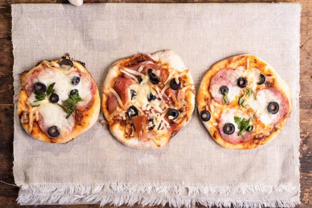 A pizza de vários ready-made mini, pizzetta com salsicha e bacon, Jamon em um guardanapo de linho em uma tabela de madeira-estilo napolitano e Romano - foto de acervo