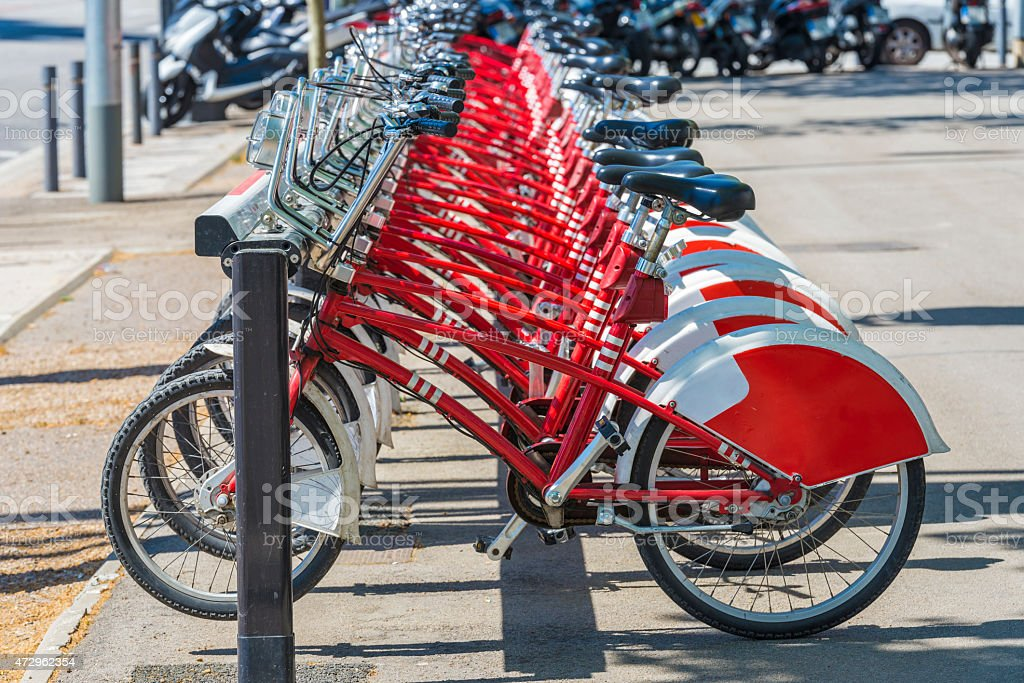 Several red and white bicycles in a row in Barcelona stock photo