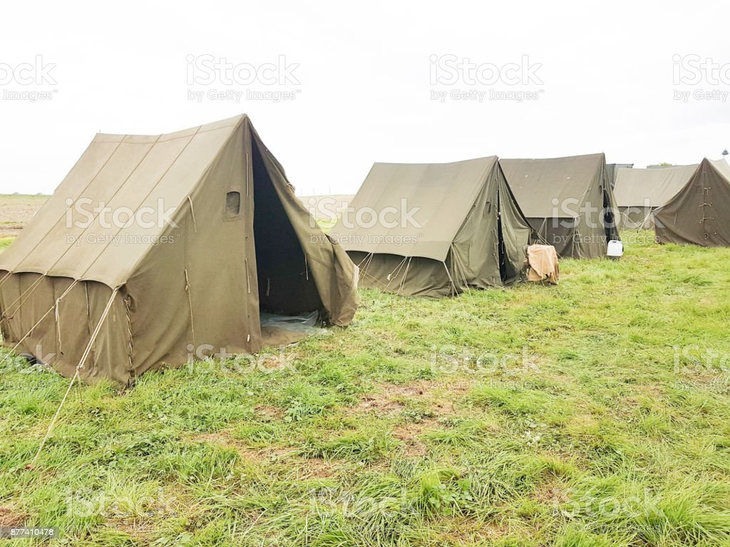 several rope vintage army military tents in a field on grass stock photo