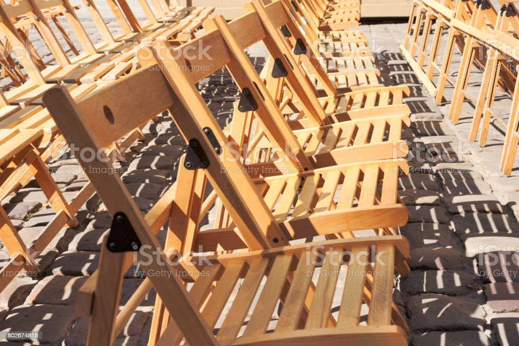 Several rows of empty wooden folding chairs in the open air