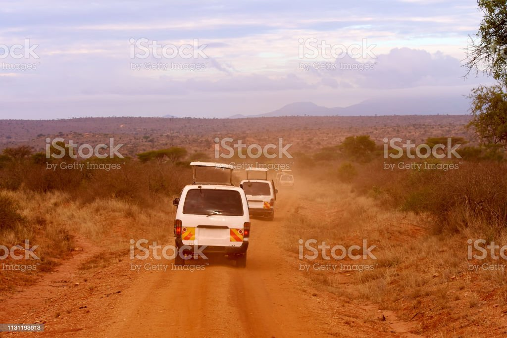 Several safari cars in Kenya in Africa, red sand and mountains in the...