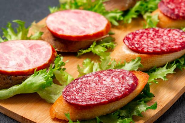 Mehrere Sandwiches mit Wurst und Salami und Sauce auf schwarzem Brett, Hintergrund mit Kopierraum – Foto