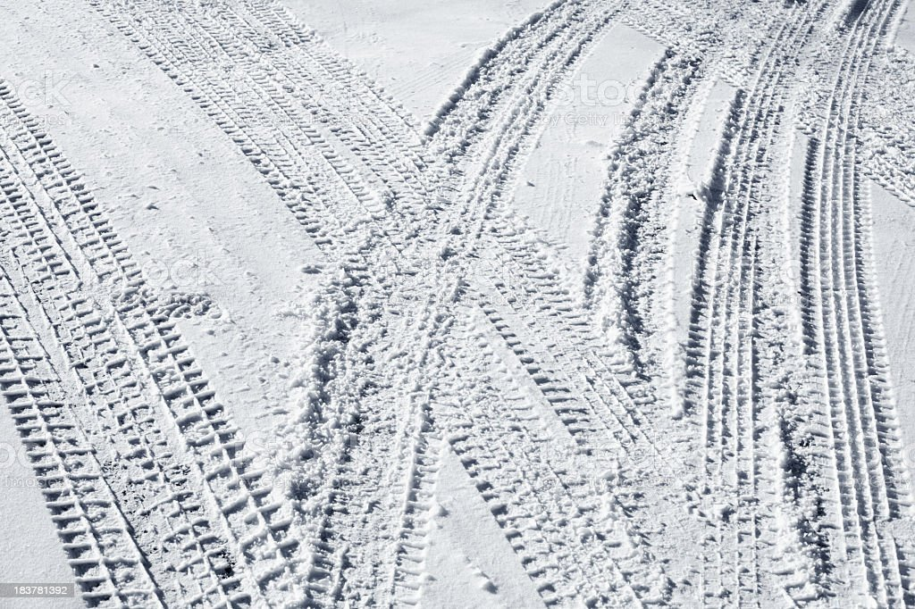 Several sets of tire tracks in the fresh snow royalty-free stock photo