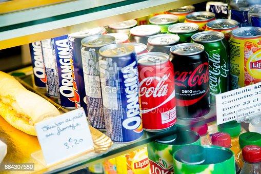 Paris, France - October 08, 2015: Several soft drink cans in a shop window. We can see various cans of Orangina, Coca Cola classic, Coca Cola Zero, Coca Cola Life, Lipton, and Jocker