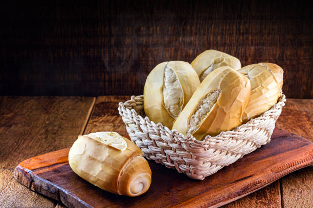 several traditional breads from brazil, on a rustic wooden background in a straw basket. National day of Brazilian French bread. several traditional breads from brazil, on a rustic wooden background in a straw basket. National day of Brazilian French bread. bread stock pictures, royalty-free photos & images