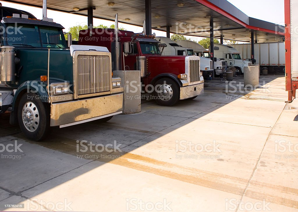 Several trucks at a rest stop gas station filling up tanks stock photo