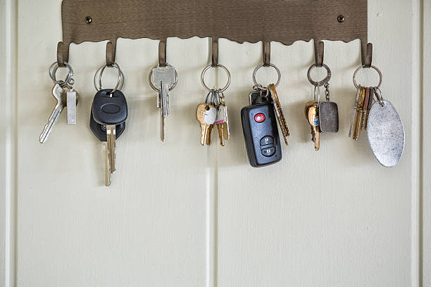 Several types of keys hanging on wall hooks stock photo