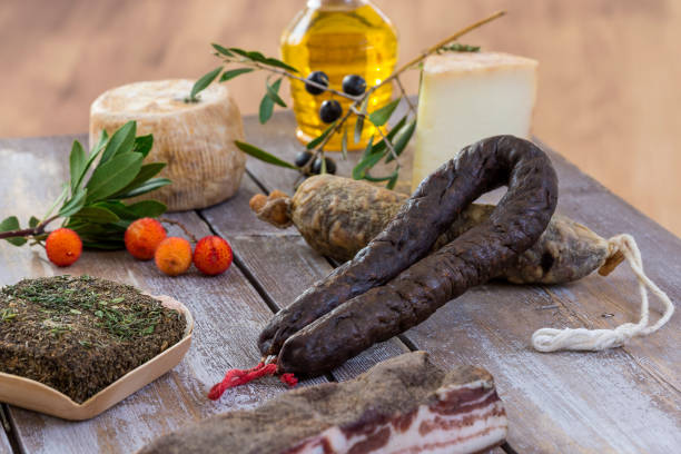 several variety of traditional Corsican charcuterie with an olive branch and black olives on wooden background stock photo
