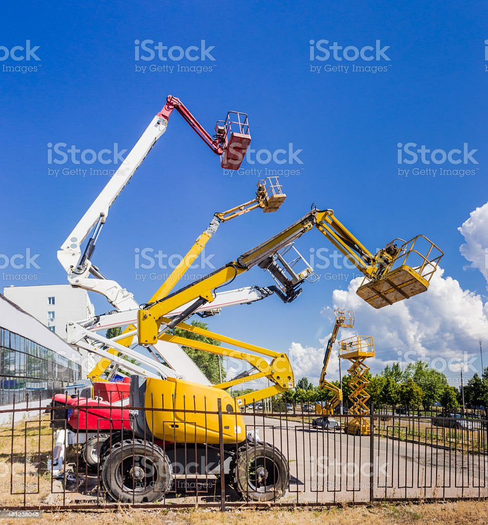 Several various self propelled articulated boom lift and scissor stock photo
