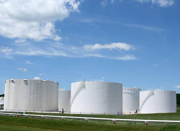 Several white storage tanks in a grassy field stock photo