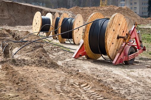 Several wooden coils with power cable laid in a trench. Concept of electricity supply for construction projects.