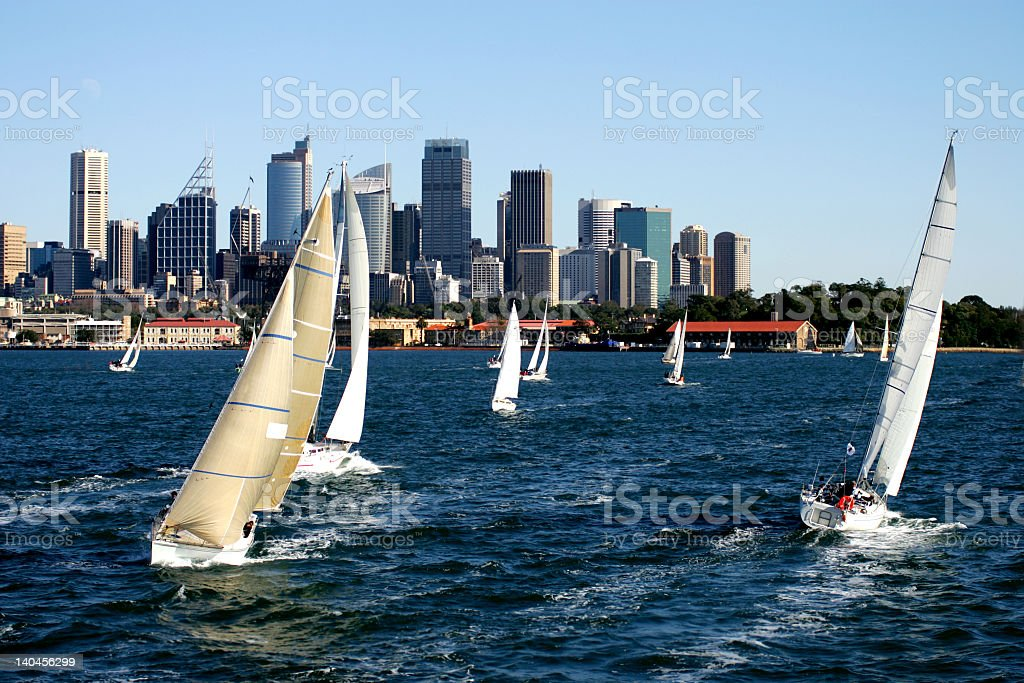 Several yacht regatta in the sea with the view of city stock photo