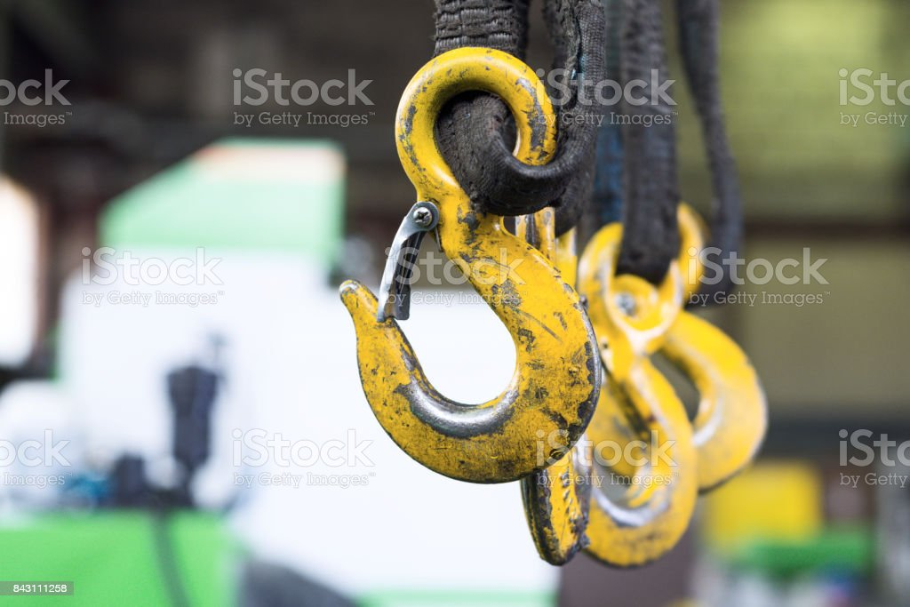 Several yellow cargo hooks hanging on dirty, oiled textile slings stock photo