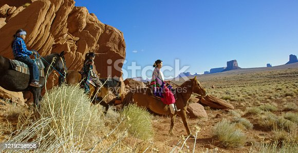 istock Several Young Native American (Navajo) Children Wearing Traditional Navajo Clothing Ride Their Horses through the Landscape of the Monument Valley Desert in Arizona/Utah Next to a Large Rock Formation on a Clear, Bright Day 1219298958