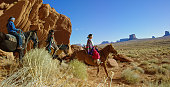 Several Young Native American (Navajo) Children Wearing Traditional Navajo Clothing Ride Their Horses through the Landscape of the Monument Valley Desert in Arizona/Utah Next to a Large Rock Formation on a Clear, Bright Day