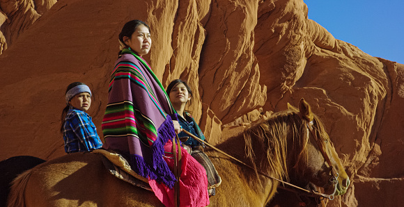 Several Young Native American (Navajo) Children Wearing Traditional Navajo Clothing and Sitting on Their Horses and Look out at the Landscape of the Monument Valley Desert in Arizona/Utah Next to a Large Rock Formation