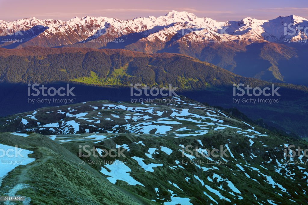 Severe mountain plateau against the background of a snow-covered range stock photo