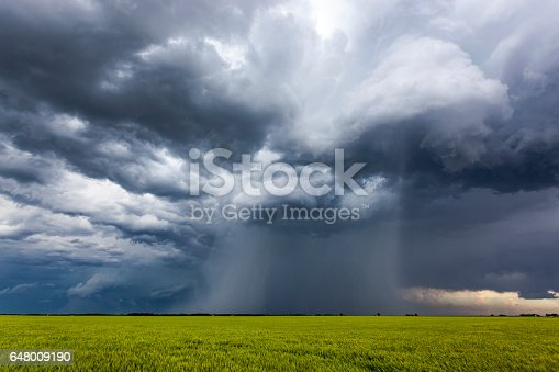 istock Severe, rotating storm clouds with torrential rain shaft over farmland 648009190