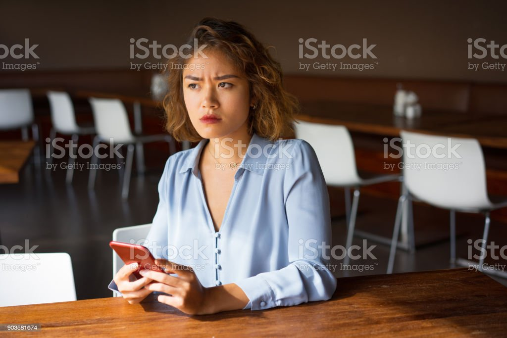 Severe Young Businesswoman with Phone at Cafe Closeup of strict young Asian woman sitting at table in cafe and holding mobile phone. Frowning business woman chatting and getting bad news. Communication and bad news concept Adult Stock Photo