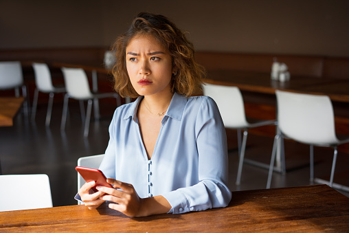 Severe Young Businesswoman With Phone At Cafe Stock Photo - Download Image Now