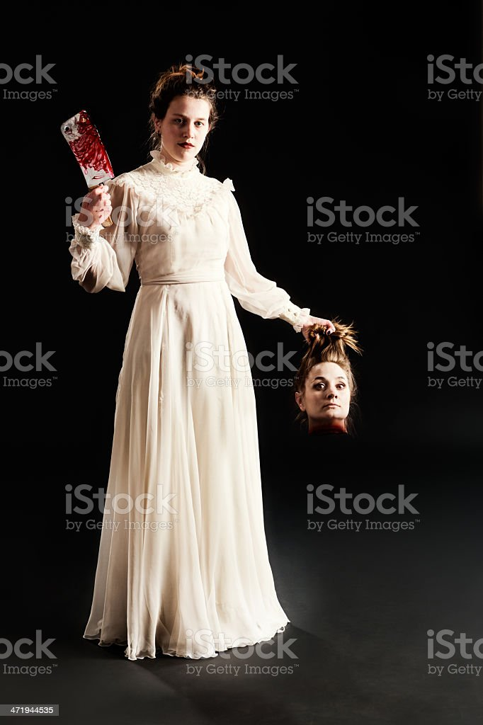 Severed head held by beautiful young Victorian axe murderess stock photo