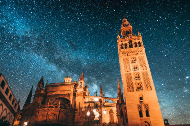 Seville at night Giralda tower under the Milky Way. Seville, Spain. santa cruz seville stock pictures, royalty-free photos & images