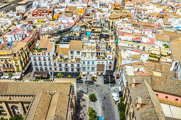 Seville Cityscape Seville, Spain - August 12, 2015: Photo taken from the the top of La Giralda. Taken during the day, and features people in the plaza below, in addition to the old city of Seville and several businesses in the background. santa cruz seville stock pictures, royalty-free photos & images