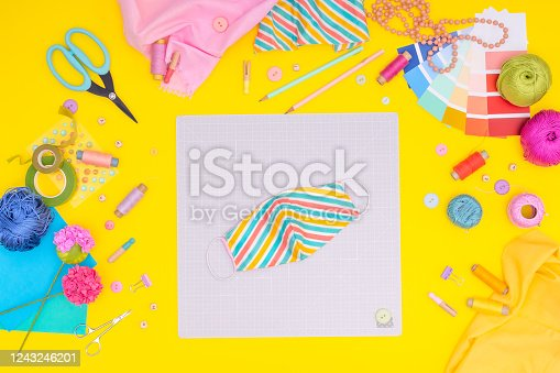 istock Sew protective mask from a colored fabric. DIY workplace with craft equipment on yellow background. 1243246201
