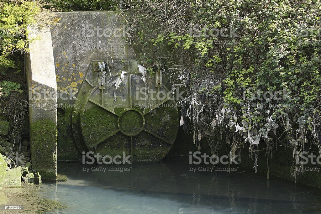Sewage Farm overflow pipe valve with raw public waste visible royalty-free stock photo