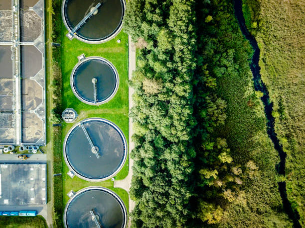 Sewage treatment plant Aerial shot of sewage treatment plant placed near a river, Denmark.  Aerial view shot with drone. sewer stock pictures, royalty-free photos & images