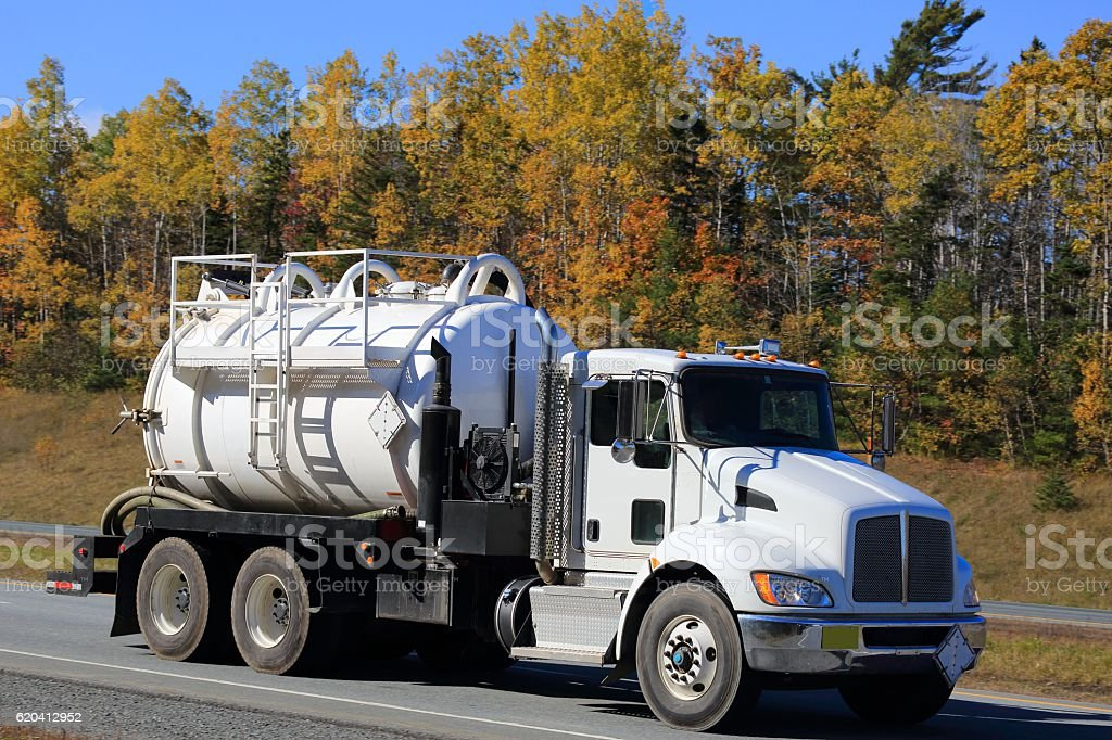 Sewage truck on an interstate, trees in background. stock photo