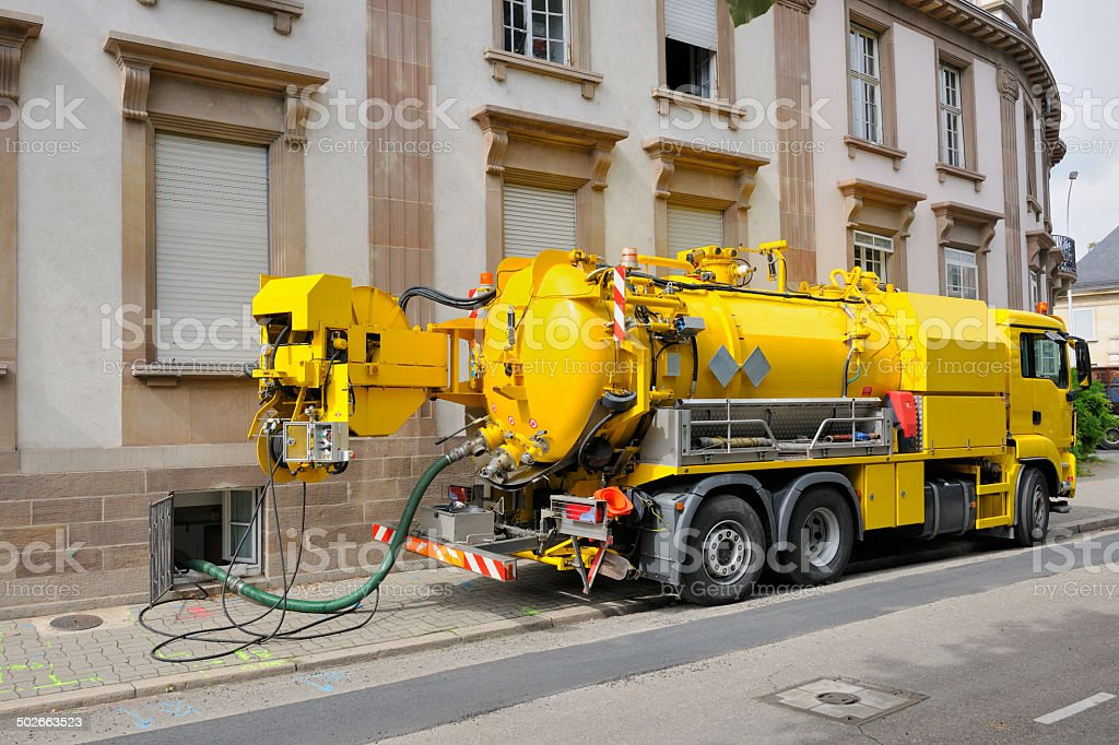 Sewage truck working in urban city environment stock photo