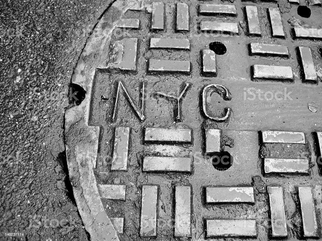 A sewer grate with an embossed NYC stock photo