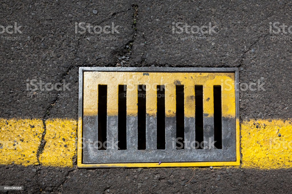 Sewer grate with yellow paint stock photo