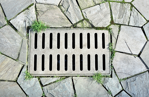 905087856 istock photo Sewer manhole cover on the stone bricks road 500898228