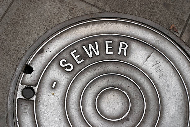 Sewer Manhole Cover A sewer manhole cover in the sidewalk that is well worn and shiny sewage stock pictures, royalty-free photos & images