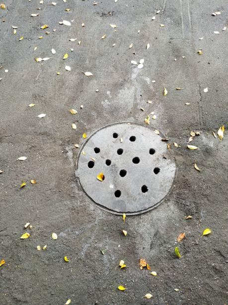 kanalisationsschacht auf schwarzem asphalt - eisenstadt austria stock-fotos und bilder