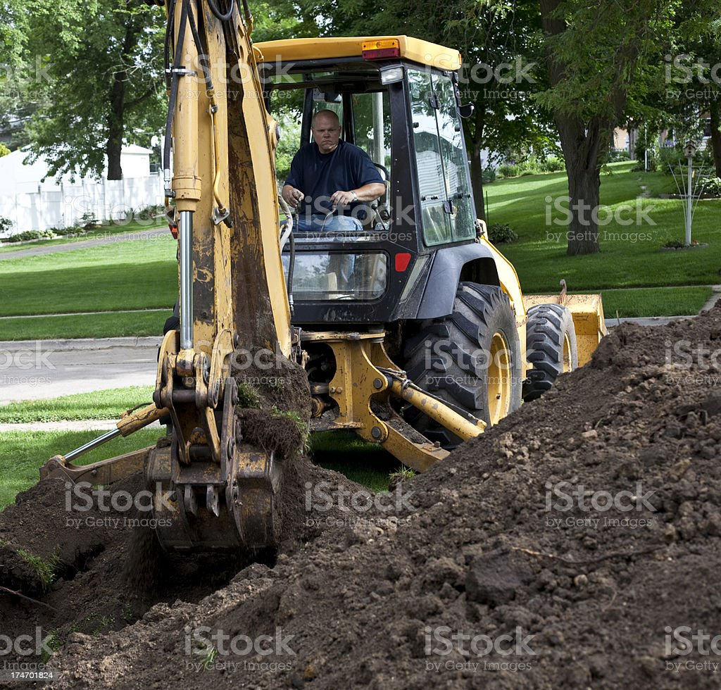 Sewer repair with construction backhoe royalty-free stock photo