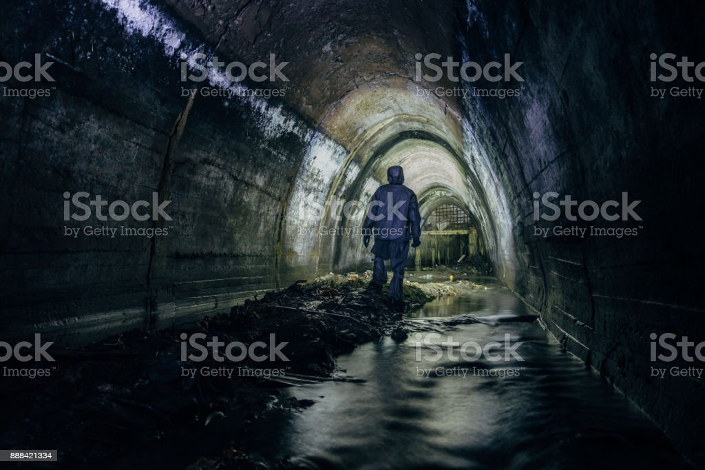 Sewer tunnel worker in chemical protective suite in underground gassy sewer tunnel stock photo