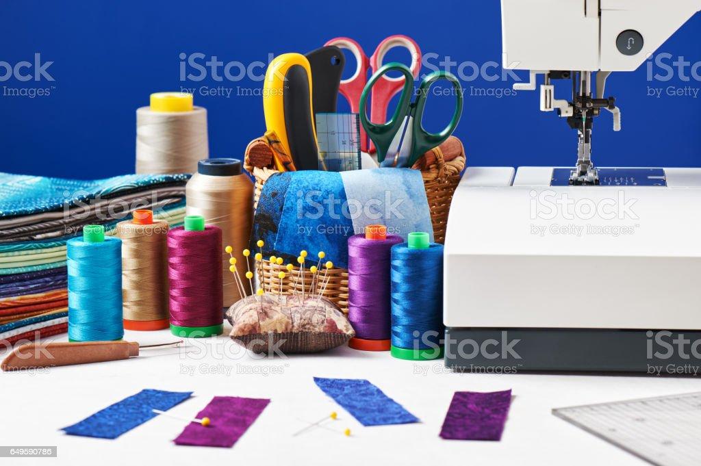 Acessórios de costura em uma cesta e carretéis de tópicos ao lado da máquina de costura - foto de acervo