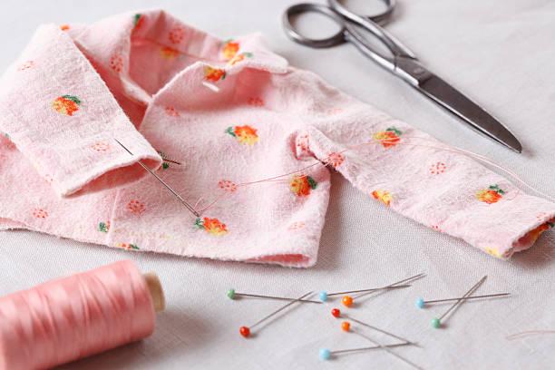 sewing baby clothes - nähpuppen stock-fotos und bilder