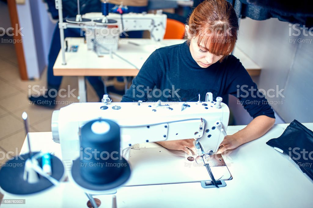Sewing dress on the sewing machine close-up stock photo