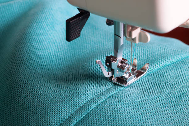 sewing machine and turquoise fabric - seam stock photos and pictures