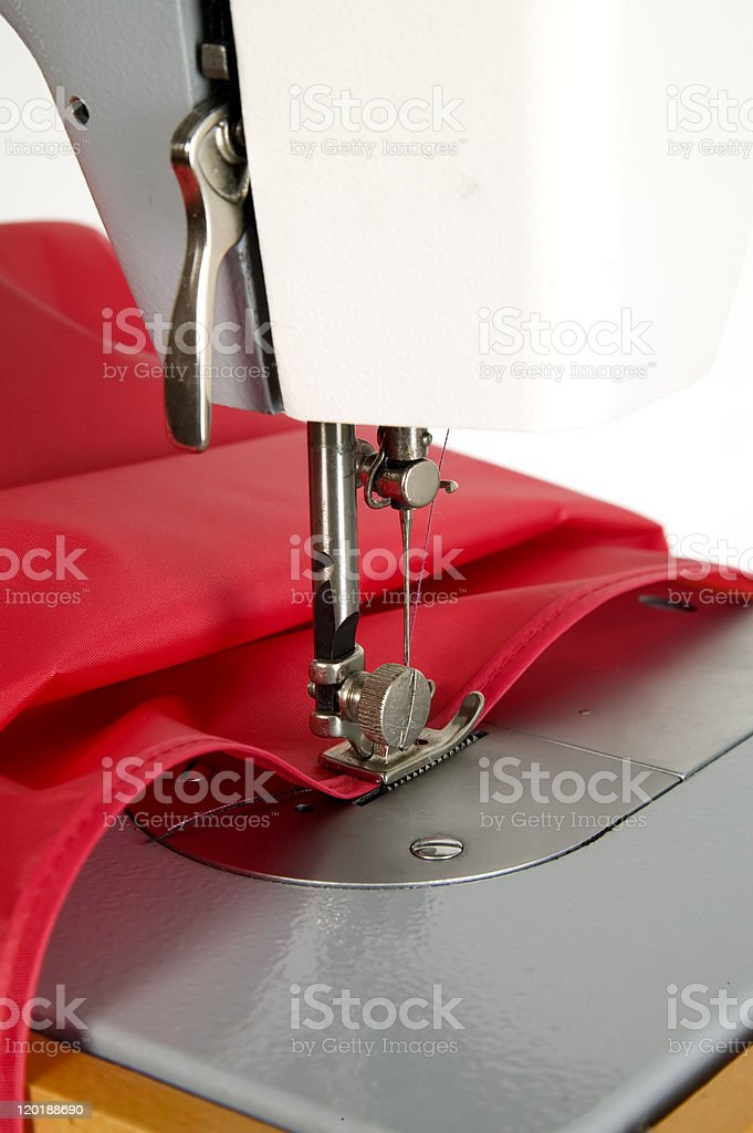 Sewing machine is stitching red fabric royalty-free stock photo