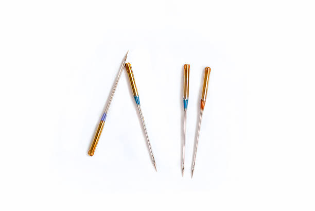 sewing machine needles - sewing machine needle stock photos and pictures