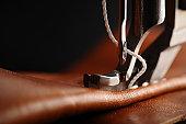 Macro, close-up of needle penetrating leather