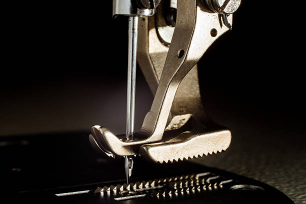 sewing machine with needle - sewing machine needle stock photos and pictures