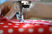 Female hands on sewing machine. Close up of seamstress work