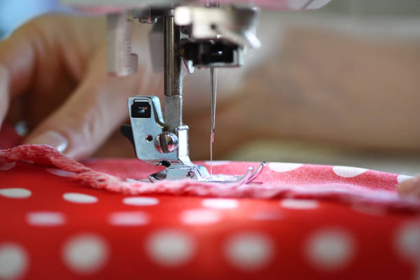 Sewing machine working part with red cloth Female hands on sewing machine. Close up of seamstress work stitching stock pictures, royalty-free photos & images